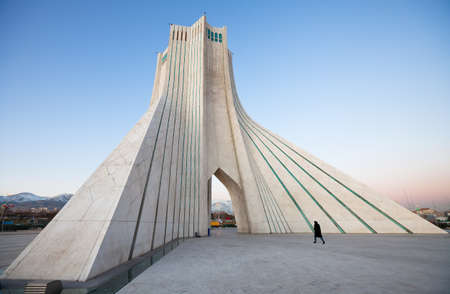 iran: Azadi monument, the famous landmark of Tehran, with a pedestrian walking by  Stock Photo