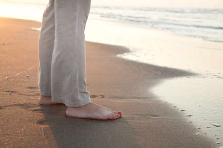 pieds nus femme: Femme aux pieds nus sur le sable dor� de la plage au coucher du soleil