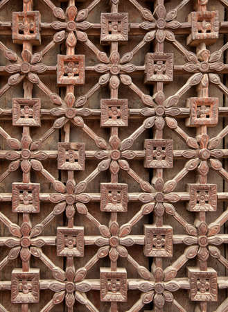 latticework: Carved wooden latticework with flowers and squares design creating a perforated wall