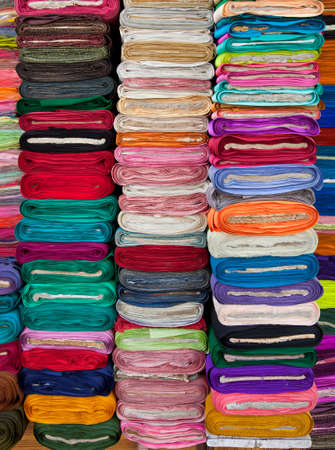 Traditional fabric store with stacks of colorful textiles  photo