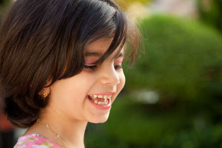 dark brown hair: Portrait of a 4 year old laughing Caucasian girl with dark brown hair