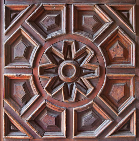 Beautiful pattern with a flower on the center carved on the surface of a wooden door  photo