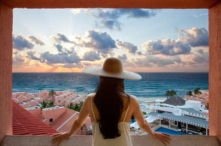 Woman with hat looking at the beach and sky from a balcony in Cancun