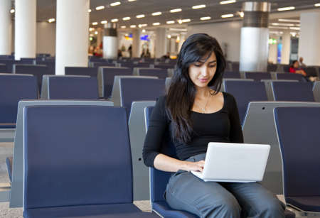 Woman working with her notebook in the airport photo