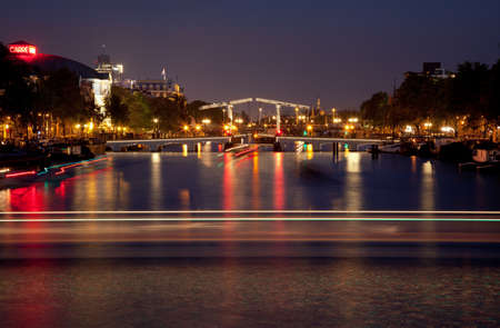 amstel river: Illuminated and reflected bascule Magere Brug Bridge on Amstel river of Amsterdam, with light trails of boats passing on the water.