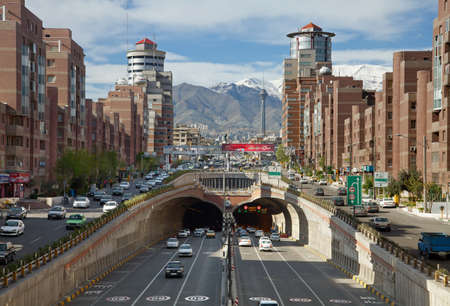 Cars Passing Through Tohid Tunnel of Tehran with Milad Tower and Alborz Mountains in the Background. Editorial