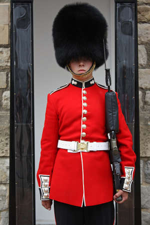 british man: Queen Guard in Red Uniform.