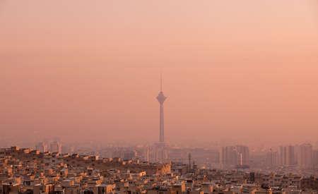 contaminacion aire: Edificios residenciales en frente de la Torre Milad en horizonte de aire contaminado de Teherán en puesta del sol rosada.