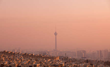air pollution: Residential buildings in front of Milad Tower in air-polluted skyline of Tehran at pink sunset.
