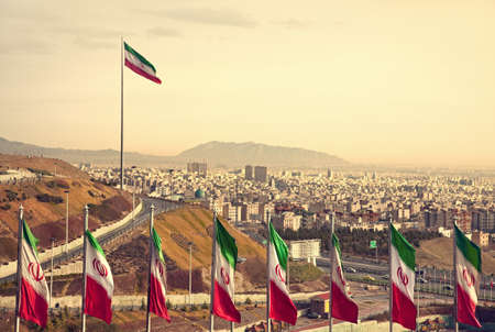 Set of Iran flags in Front of Tehran Skyline and one large flag in the background at sunset with orange warm tone. Stock Photo