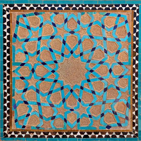 arabesque antique: Traditional old Islamic design with flowers and stars made of brown clay and blue tiles in Yazd. Stock Photo