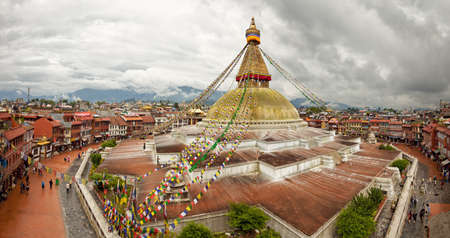 Sacred Boudhanath buddhist stupa and adjacent buildings in Kathmandu of Nepal against Cloudy Sky, shot from above. Stock Photo
