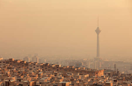 air view: Residential buildings in front of Milad Tower in air-polluted skyline of Tehran illuminated with golden sunset.