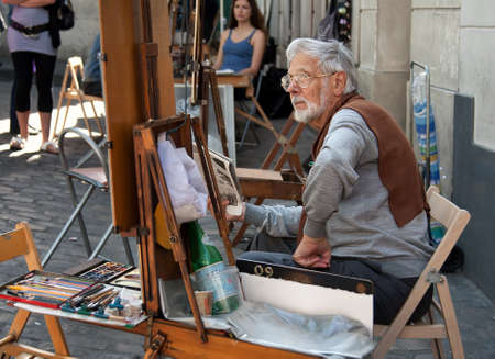 street painting: PARIS, FRANCE - JUNE 07, 2010: Painter and his easel in Place du Tertre of Montmartre, which is a cobbled square and a hangout for buskers and artists painting landscapes and tourist portraits.