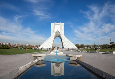 reflection: Azadi monument and its reflection on waterways in Azadi square of Tehran, against blue sky and white clouds.