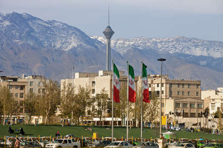 Three waving Iran flags in front of residential buildings, Milad Tower and Alborz Mountains in the city of Tehran.