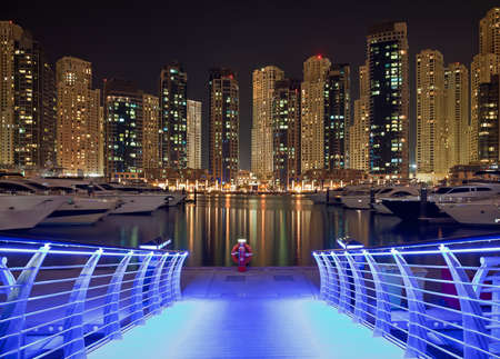 luxury modern: Skyscrapers of Dubai Marina against black sky, behind a pier bridge illuminated with blue light. Dubai Marina is an artificial canal city, carved along a two mile stretch of Persian Gulf shoreline.