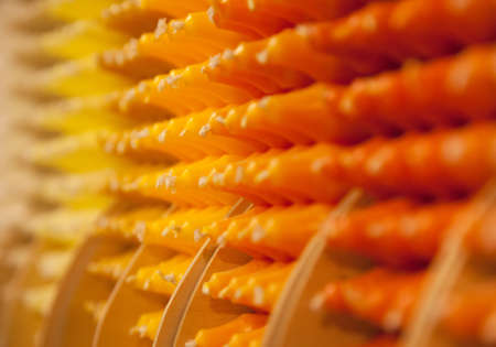 tonality: Colorful stick candles with orange and yellow tonality, arranged in shelves and sorted by color in a candle shop.