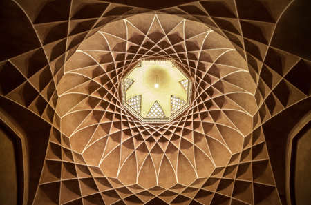 plasterwork: Old brown plasterwork with geometric Persian design inside dome of Governor Pavilion at Dolat Abad Garden of Yazd.