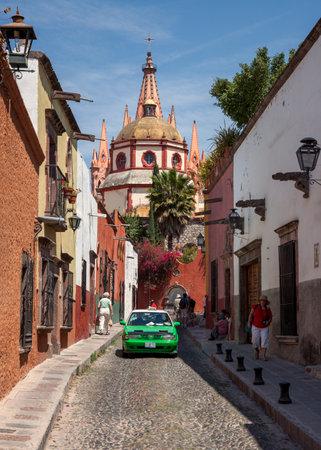 san miguel arcangel: SAN MIGUEL DE ALLENDE, MEXICO - 26 de marzo de 2011: de taxi verde delante de Parroquia de San Miguel Arcángel. La fachada gótica de esta iglesia parroquial se inspiró en Sagrada Familia.