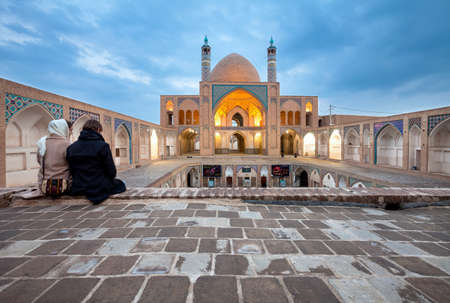 KASHAN, IRAN - March 08, 2017: Young couple visiting Agha Bozorg Mosque as tourists. This Mosque was constructed for prayers and theological sessions held by Molla Mahdi Naraghi known as Agha Bozorg. Editorial