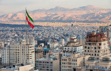 Waving Iran flag above skyline of Tehran at sunset. Stock Photo