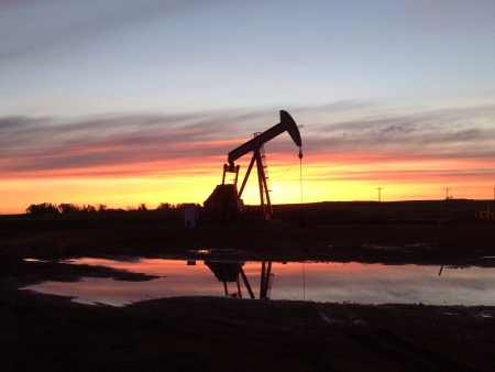 A pump jack silhouette in the sunset.  Stock Photo
