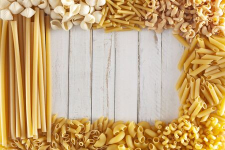 different type of pasta make a frame around a white rustic wooden table