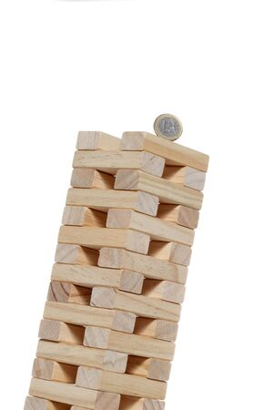 toy wooden blocks tower with a 1 euro coin on the top inclined until falling isolated on white background with copy space 写真素材