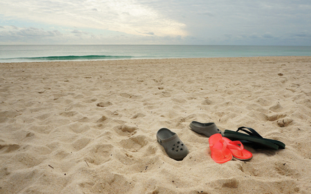 Slippers on the sandy beach against ocean and sky
