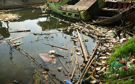 Abandoned fishing boat and lots of plastic waste floating the river bank