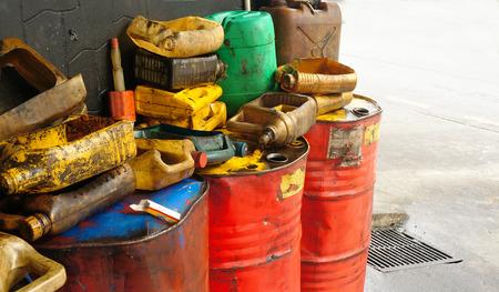 Vuile en olieachtige plastic jerrycans op de tank van afgewerkte olievaten