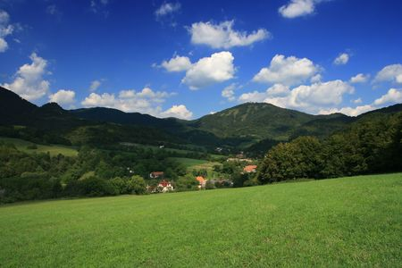 Small slovakian village in the valley surrounded with green fields and hills