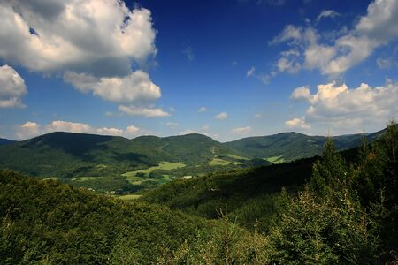 Landscape with green hills and forests and blue sky with clouds.