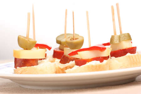 Several finger foods with olives on a plate
