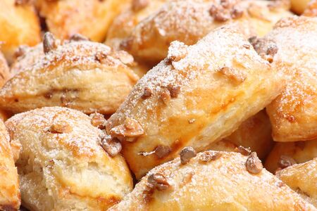 Crisp puff cakes with pieces of walnuts strewn with sugar