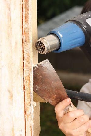 Windows renovation: removing old paint using scraper and heat gun