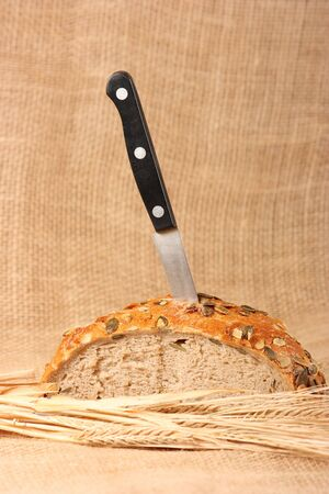 Black knife in bread with pumpkin seeds and barley spikes