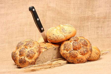 Various types of baked goods with spikes of grain and black knife Stock Photo