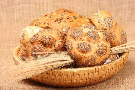 Various types of baked goods on trug with spikes of grain