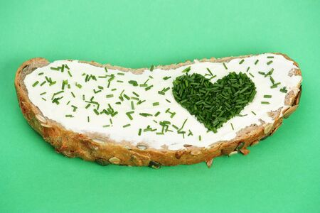 Slice of bread with butter and heart made of cut chive in shape of heart photo