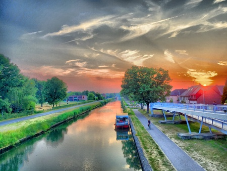 dramatic sky: Dramatic Sky over a Canal with a yacht Stock Photo