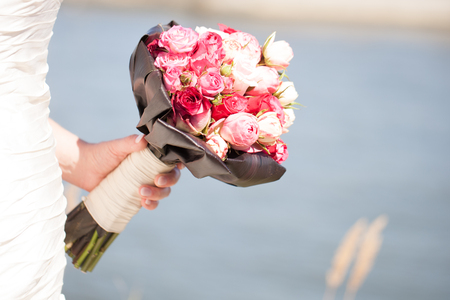 arm bouquet: Bride wearing a white wedding dress and holding her bright pink wedding bouquet Stock Photo