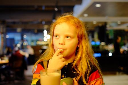 Adorable little girl eating icecream licking fingers Standard-Bild