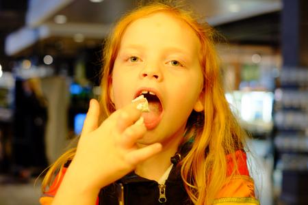 Adorable little girl eating icecream licking fingers 写真素材