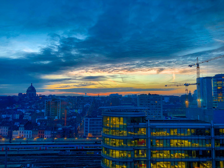 Colorful and dramatic sunrise or sunset over the financial business district of the city of Brussels, Belgium, Europe, showing a colorful sky reflected in the glass windows of the office buildings