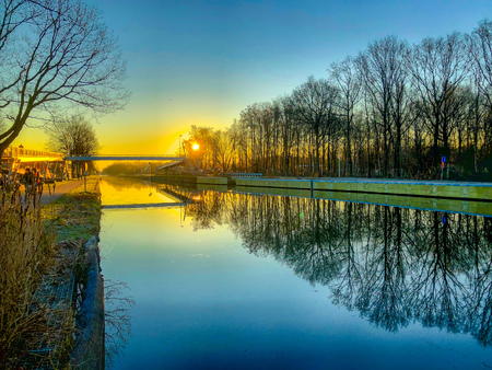 Dramatic and colorful sunrise or sunset over a beautiful landscape with a river or canal, treelined riverside and grass at sunrise creating a tranquile and quiet scenic nature background 写真素材