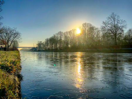 Alba o tramonto drammatico e colorato su un bellissimo paesaggio con un fiume o un canale, la riva del fiume alberata e l'erba all'alba che creano uno sfondo naturale tranquillo e silenzioso