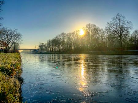 Dramatischer und farbenfroher Sonnenaufgang oder Sonnenuntergang über einer wunderschönen Landschaft mit einem Fluss oder Kanal, einem von Bäumen gesäumten Flussufer und Gras bei Sonnenaufgang, die einen ruhigen und ruhigen Naturhintergrund schaffen nature
