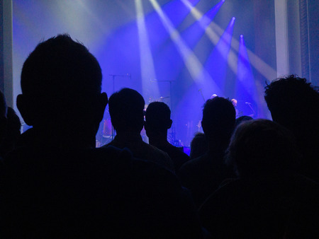Silhouettes of a crowd of people in front of a well backlit stage on which a rockband is performing